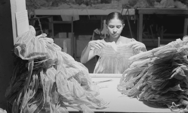 A woman makes dresses in a needlework factory in San Juan