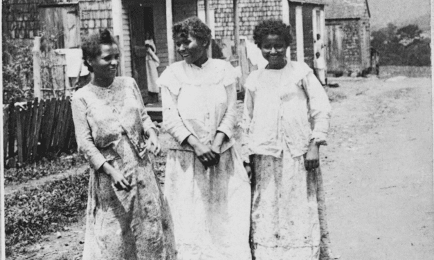 Three native Puerto Rican women in front of their hut houses