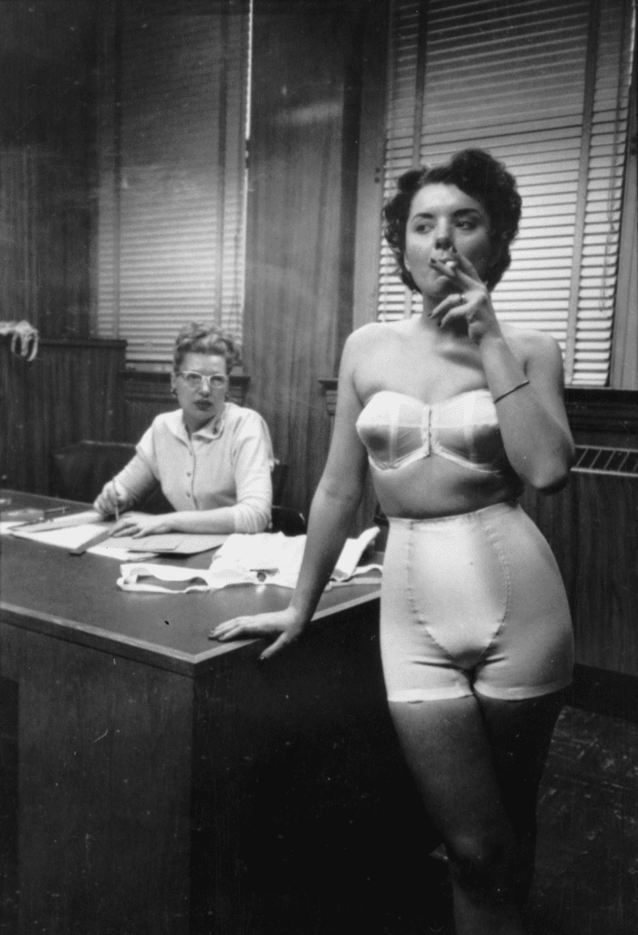 A photograph by Stanley Kubrick depicting a woman smoking a cigarette in an office