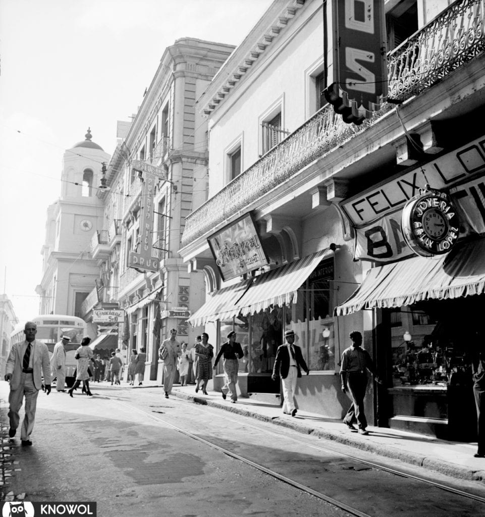 San Juan Puerto Rico Street Scene shows men walking on a street lined with stores. December, 1941.