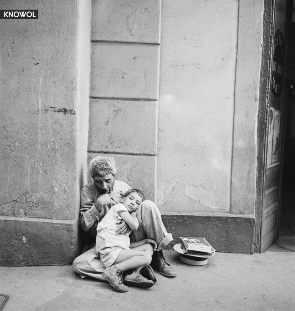 An older man, who seems to be a street beggar, sitting against a wall while cradling a poor child in San Juan, Puerto Rico.