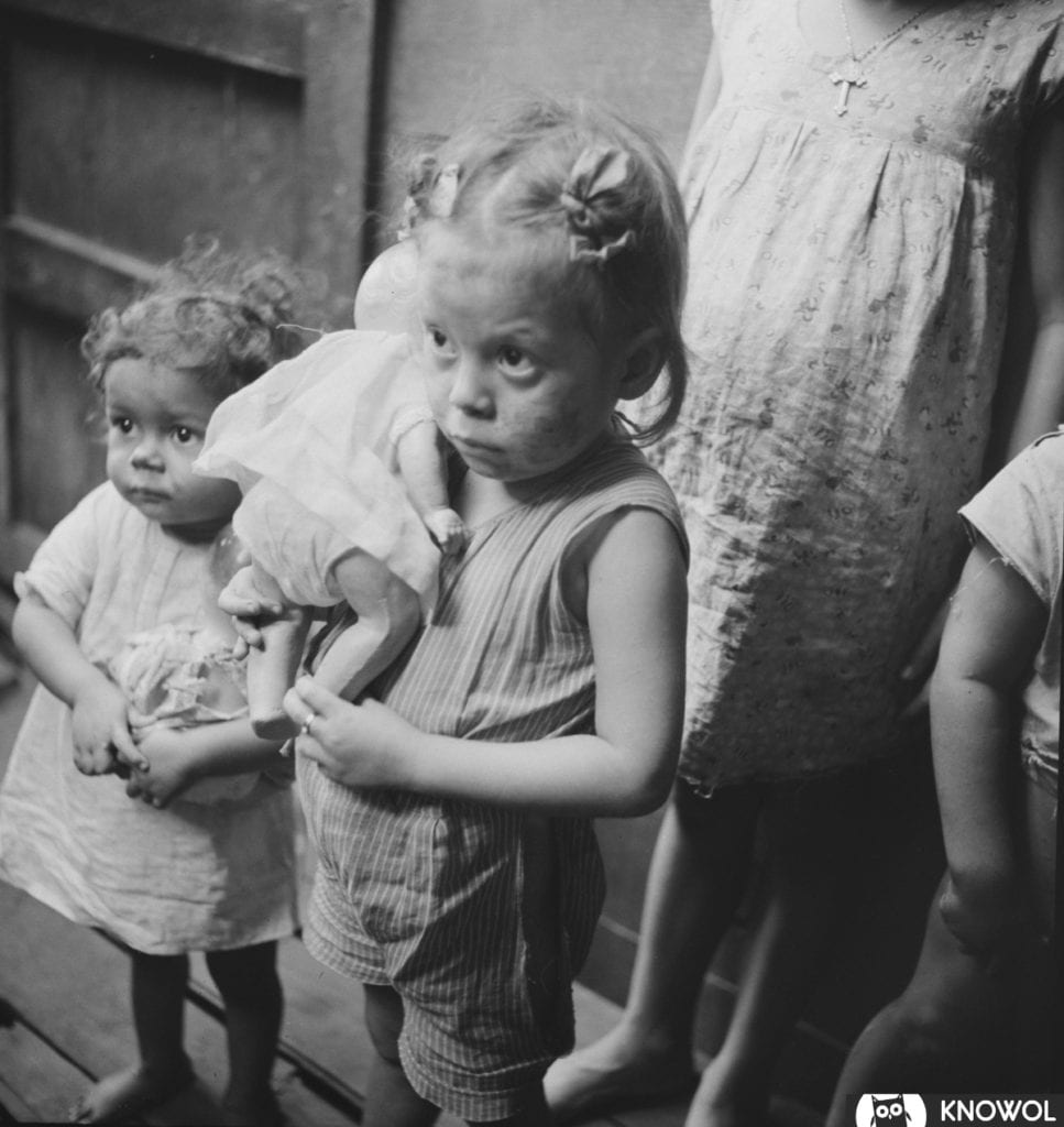 Children from La Perla, the slum area of San Juan Puerto Rico. Two small girls, each clutching a doll.