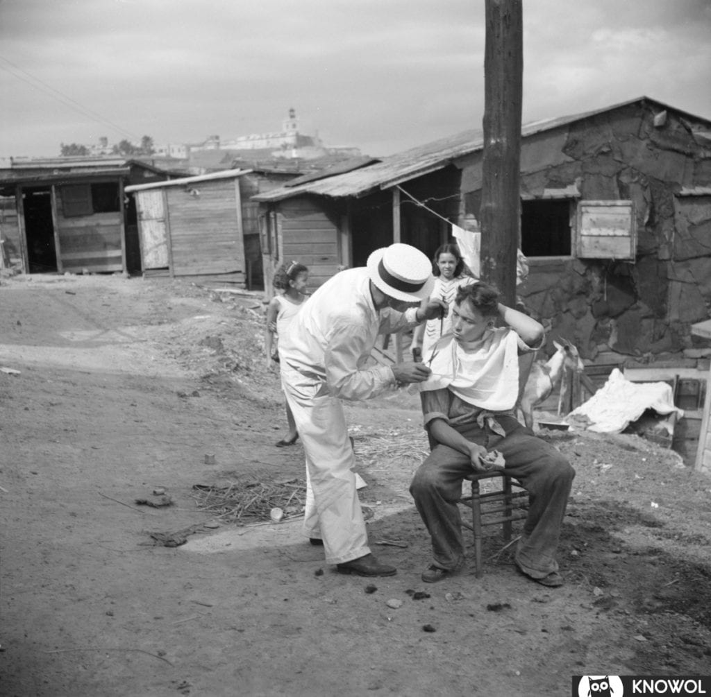 Barber cutting a man's hair outside, surrounded by shacks.
