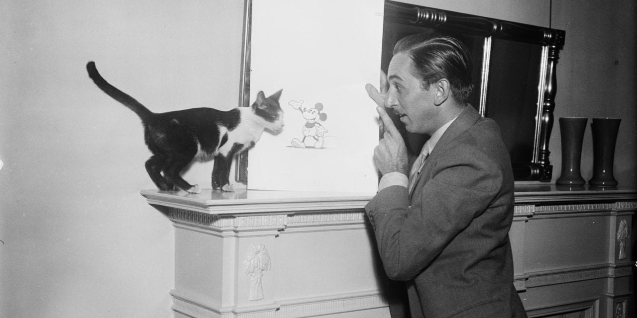 Walt Disney Showing a Picture of Mickey Mouse to a Cat